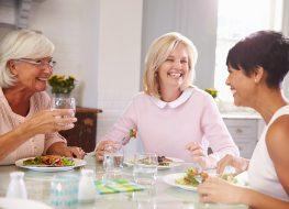 mature women eating dinner together smiling