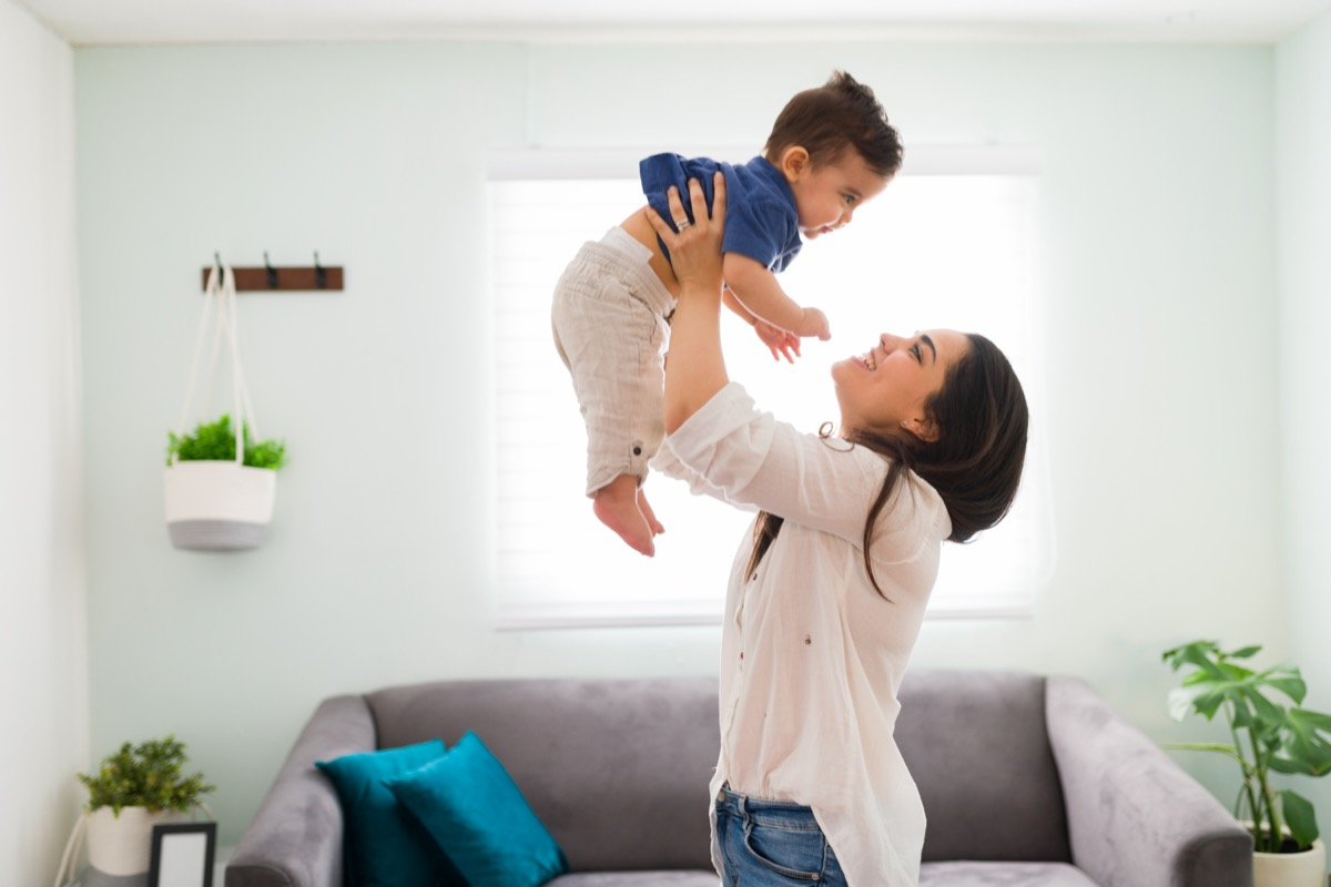 Happy young woman holding up her baby boy up while standing in living room
