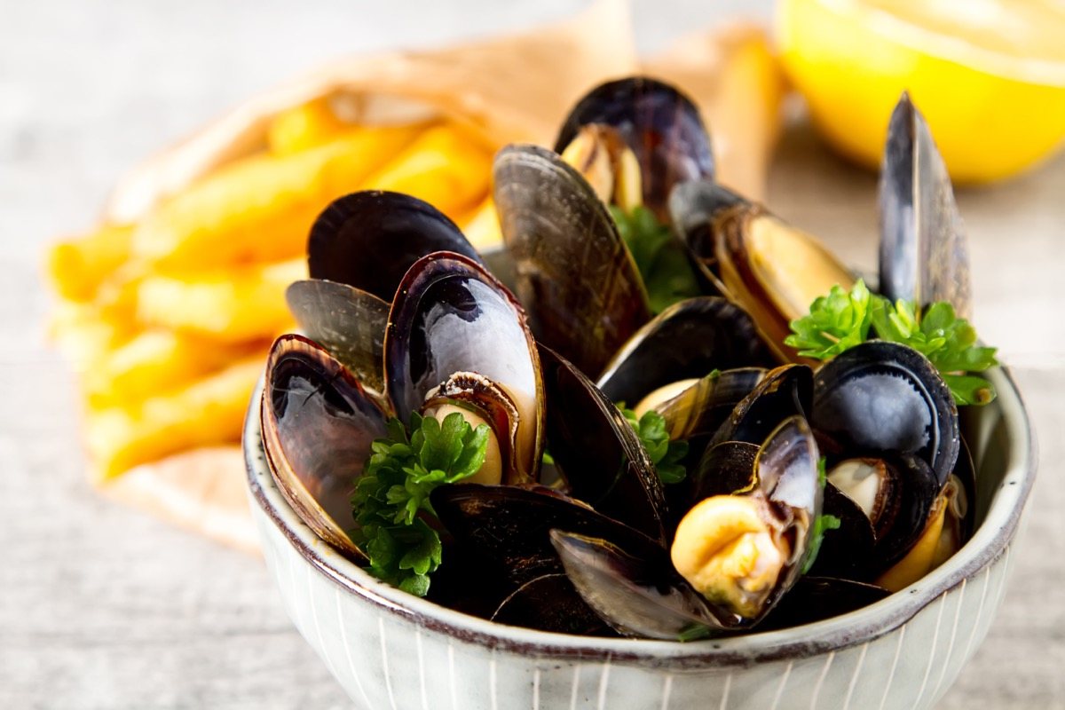moules frites in a white bowl at restaurant