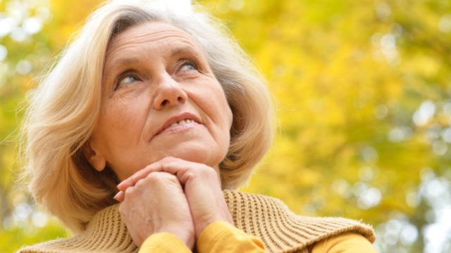 Nice,Older,Woman,Stands,On,A,Background,Of,Yellow,Autumn