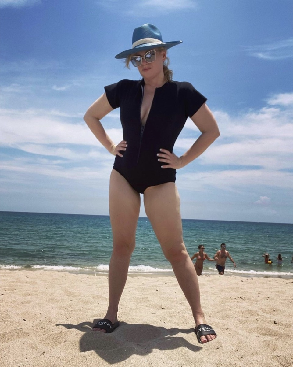 rebel wilson in black swimsuit and hat on the beach