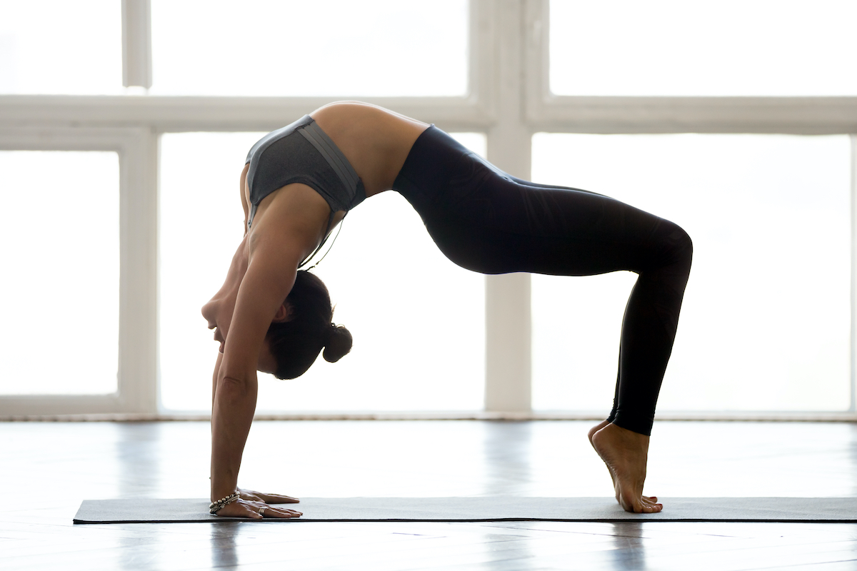 Young sporty attractive woman practicing yoga, doing Reverse Table Top exercise, Bridge pose, working out, wearing sportswear, grey pants, top, indoor full length, at yoga studio, side view