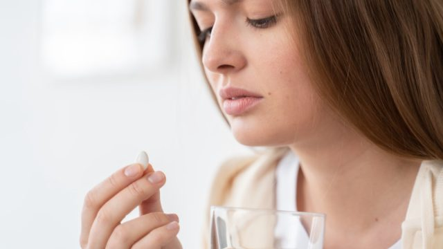 Woman holding pill in one hand and glass of water in another.