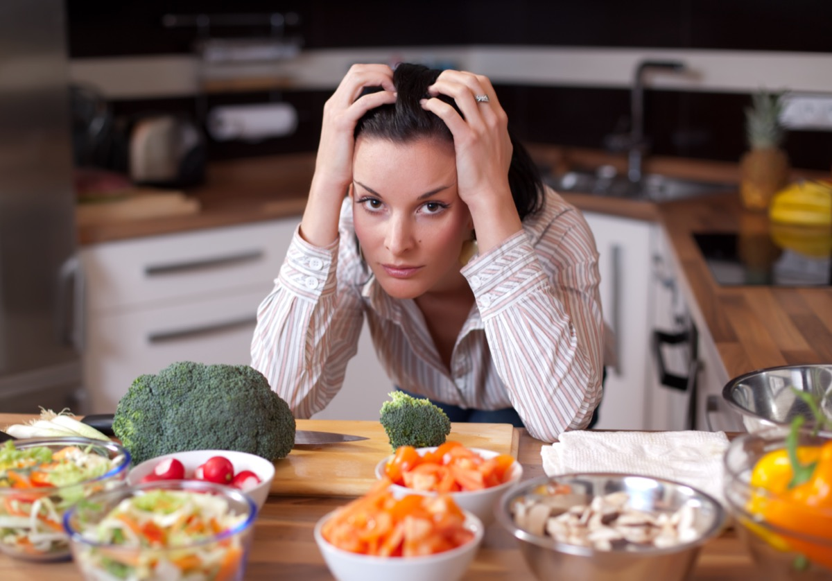 Sad woman looking out at salad bowls in her kitchen.