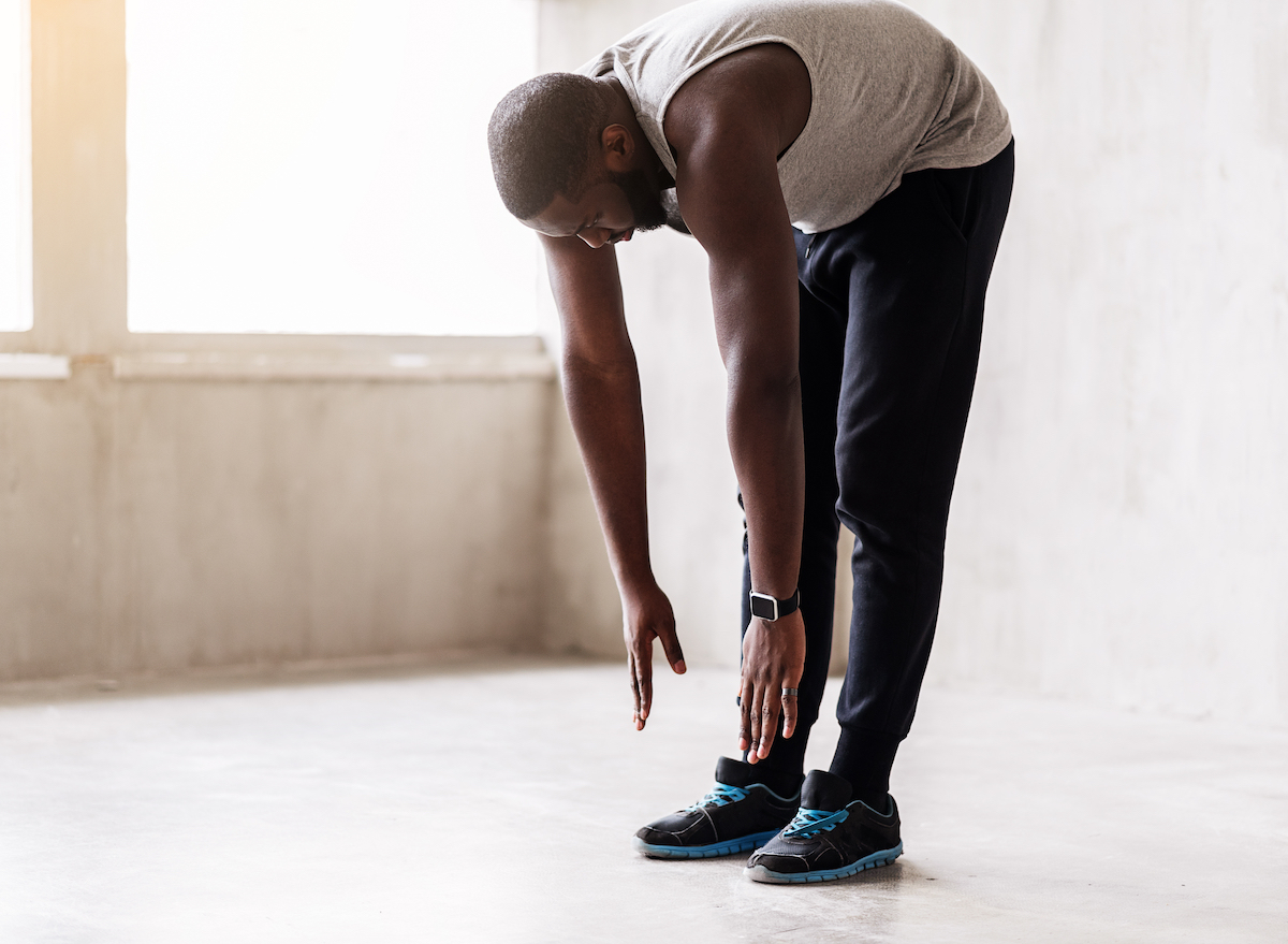 man-leaning-forward-stretching-fitness-clothing