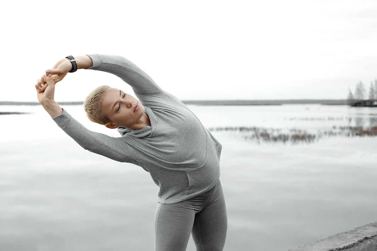 Active lifestyle, yoga, fitness and sports concept. Outdoor view of strong felxible young Caucasian female runner stretching arms, bending to one side, warming body before morning run along river bank