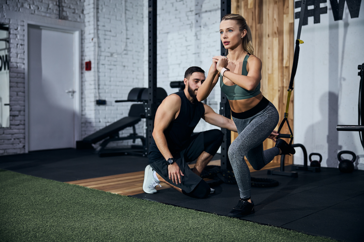 Person locking her hands together while doing a single-leg squat with an instructor placing her leg in a strap loop