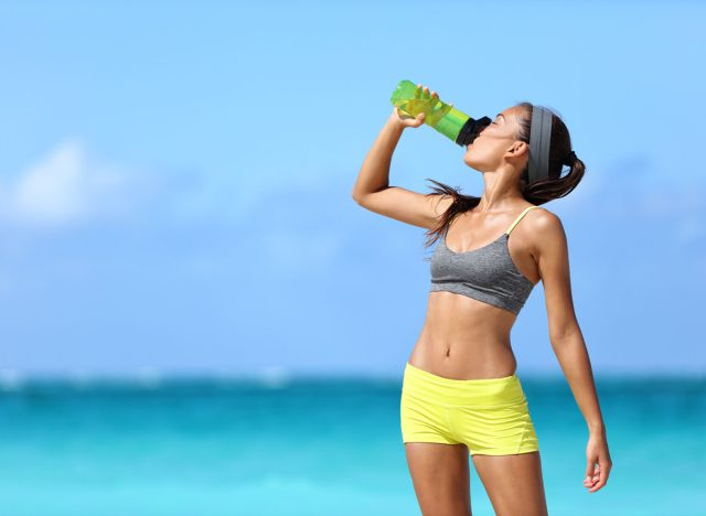 woman drinking water on beach
