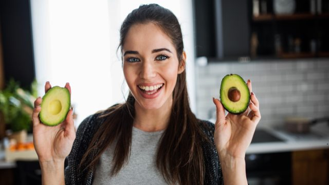Smiling woman in her kitchen holding avocado.