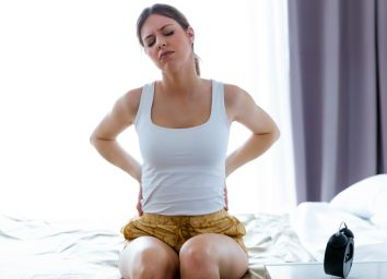 tired young woman with back pain sitting on the bed at home