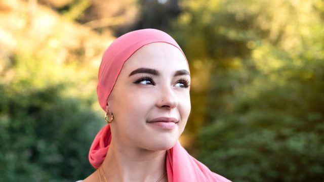 Woman,With,Cancer,Wearing,A,Pink,Scarf,Looking,Optimistic