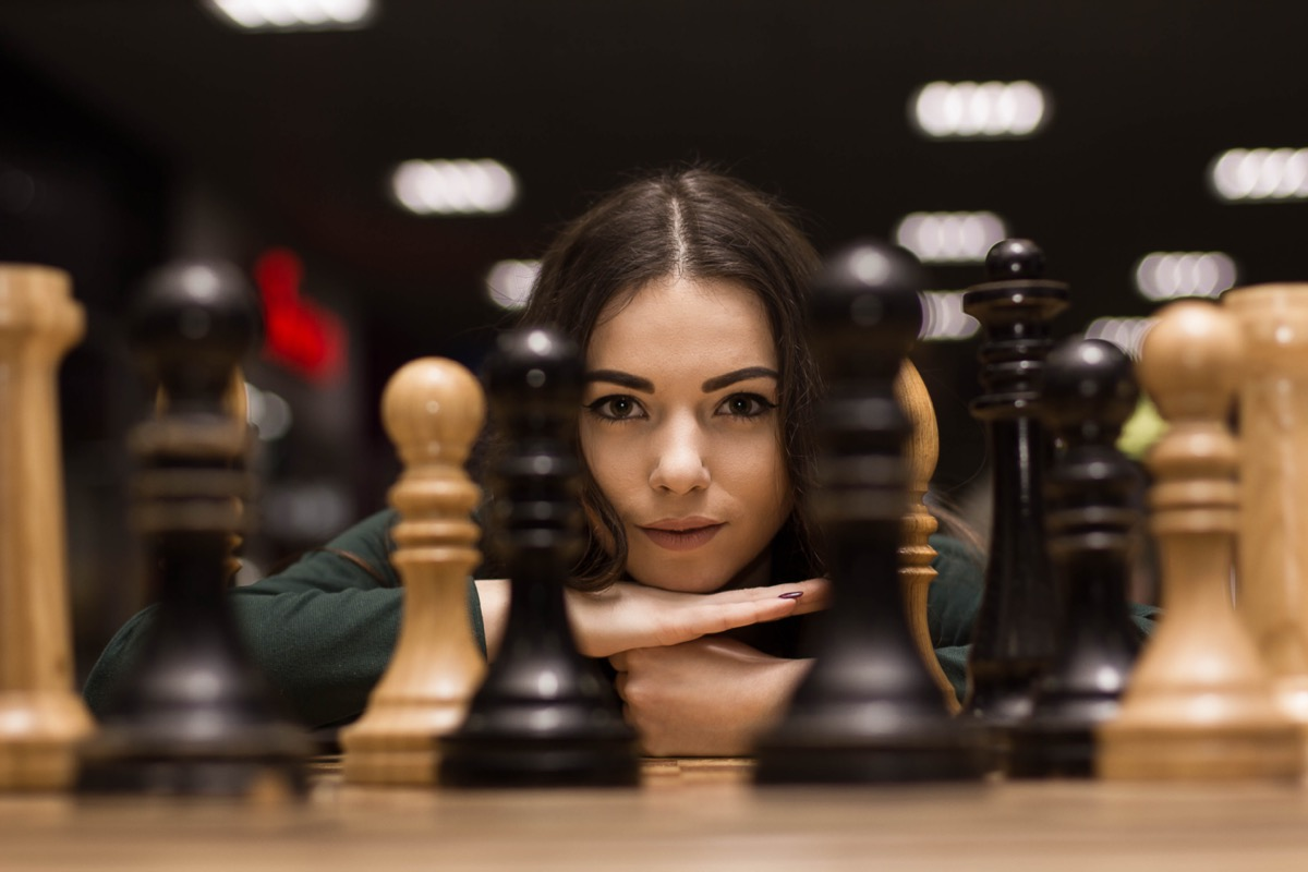Woman looking at chess pieces.