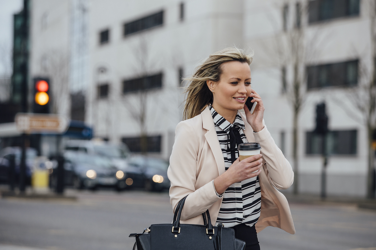Businesswoman is walking to work in the city. She is holding a coffee cup and is talking on the phone.
