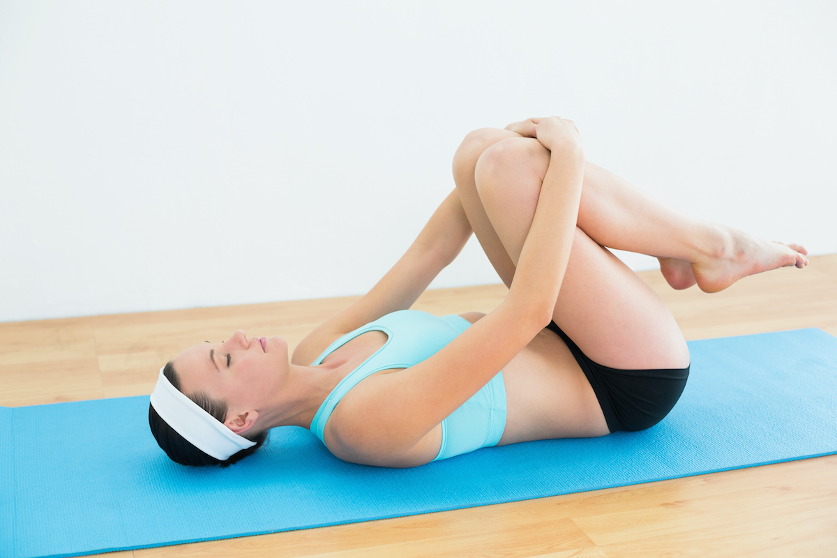 Side view of a slender young woman in supine wind release posture on yoga mat at fitness studio