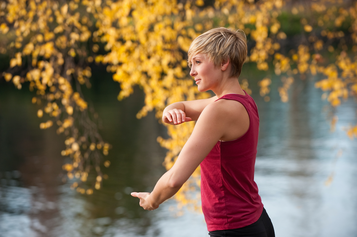 A young woman doing Tai Chi by a river