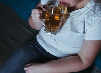 woman in white t-shirt drinking beer in the dark
