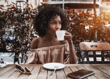 young woman in off-the-shoulder top drinking coffee outside