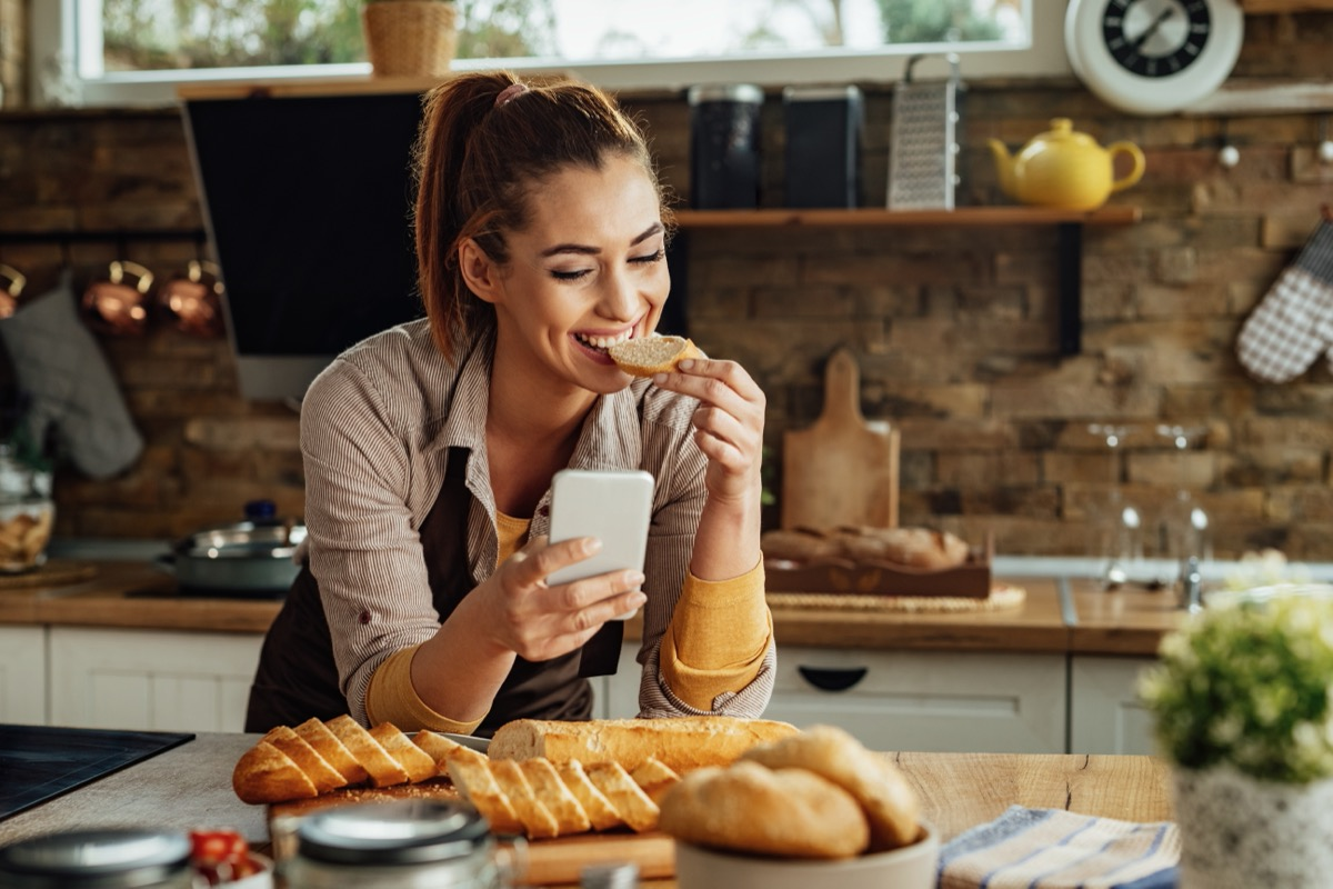 woman eating bread while text messaging