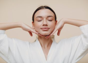 Young woman doing face building yoga facial gymnastics self massage and rejuvenating exercises