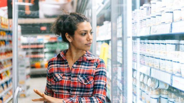Latin woman shopping in supermarket refrigerators