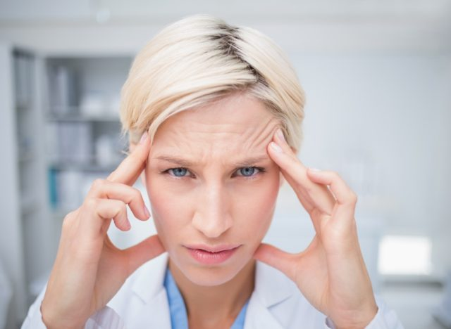 Portrait of female doctor suffering from headache in clinic