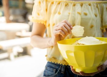 woman in yellow shirt holding yellow bowl of chips