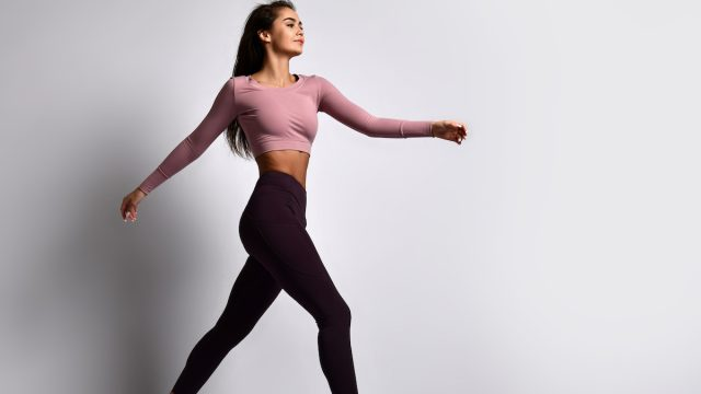 Young athletic woman brunette girl in a good shape with hair in a ponytail in trendy sportswear gym uniform jumps dances does exercises workout isolated on gray background walking