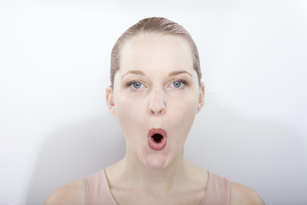 facial gymnastics. the girl does massage and rejuvenating exercises for the face
