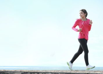 Beautiful healthy woman in pink running on the beach