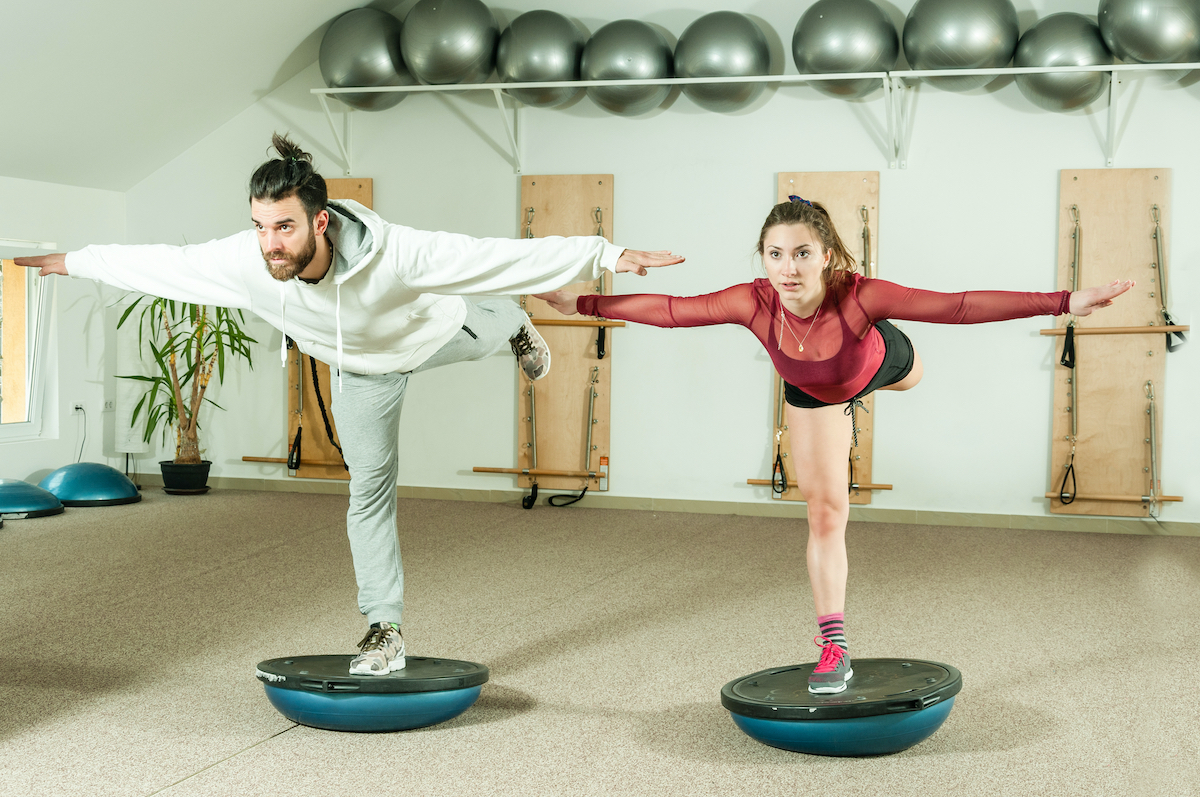 Young beautiful and attractive fitness couple workout on their balance by standing on the half ball on the one leg
