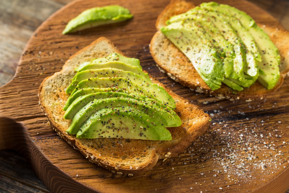 two slices of avocado toast on wooden cutting board