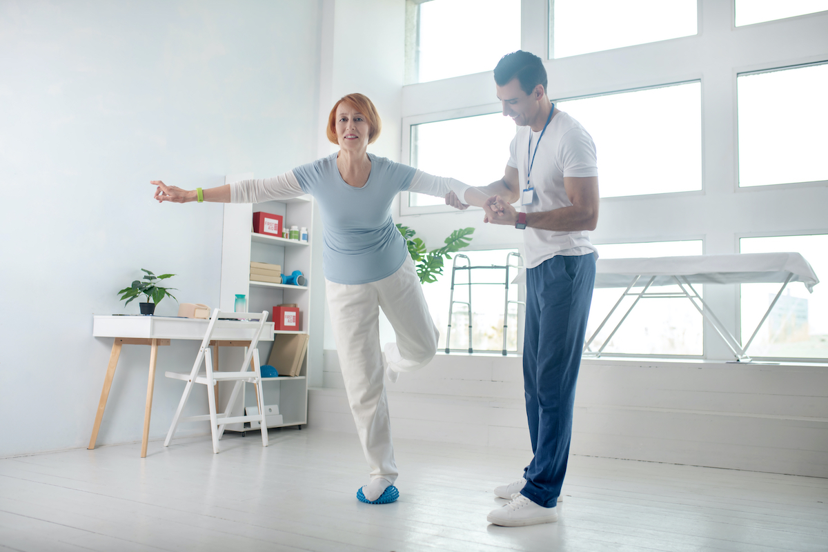 Balance exercise. Positive aged woman standing on one leg while holding the hand of her instructor