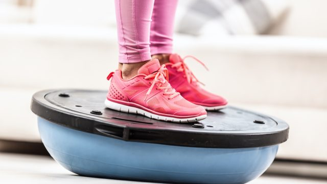 Woman in training shoes stands on a blue balance ball.