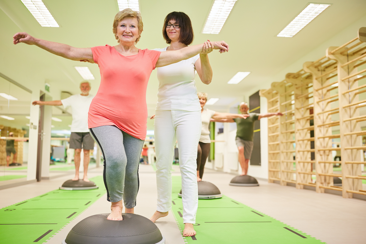 Trainer gives senior help with balance training at the Bosu Ball in the fitness class