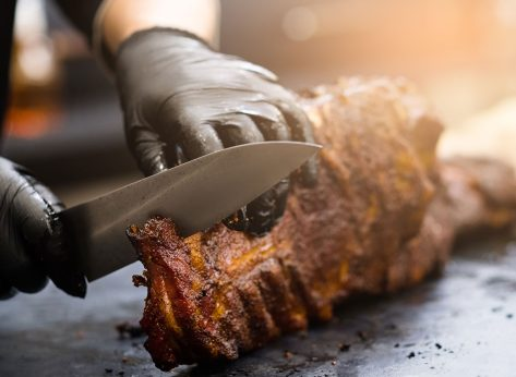 cook cutting bbq meat