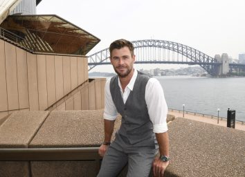 chris hemsworth in gray vest, gray pants, and white shirt sitting on a ledge at sydney opera house
