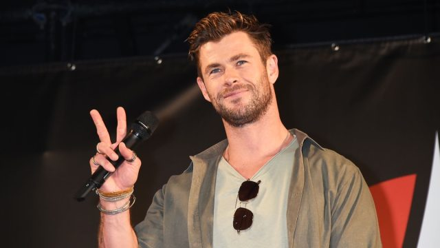 chris hemsworth in green jacket and gray t-shirt giving peace sign on stage