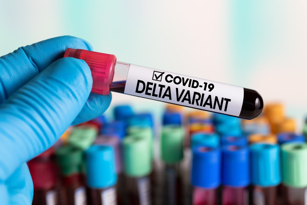 Technician holding tube of blood test identified with the label Covid-19 DELTA Variant.