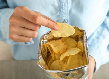 person in blue button down eating from bag of chips
