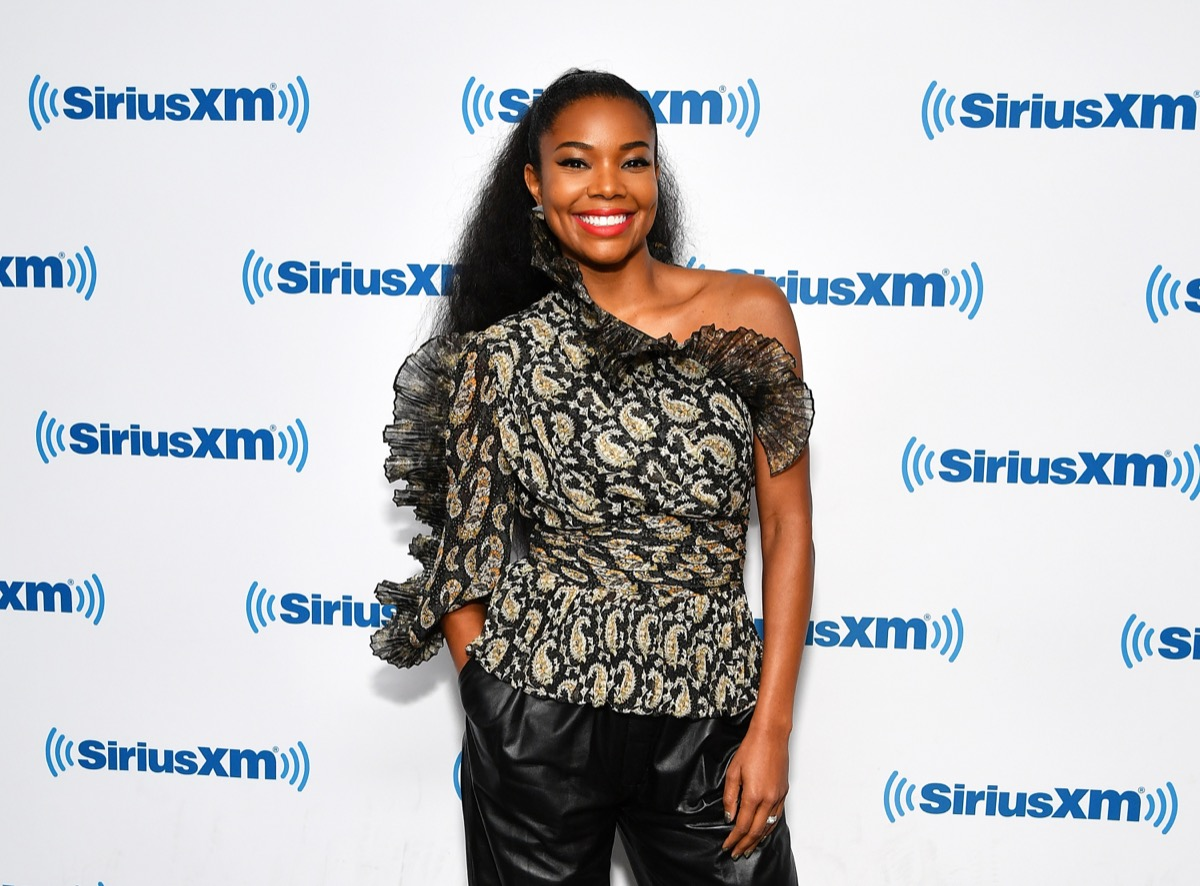 gabrielle union in black off the shoulder top and red lipstick