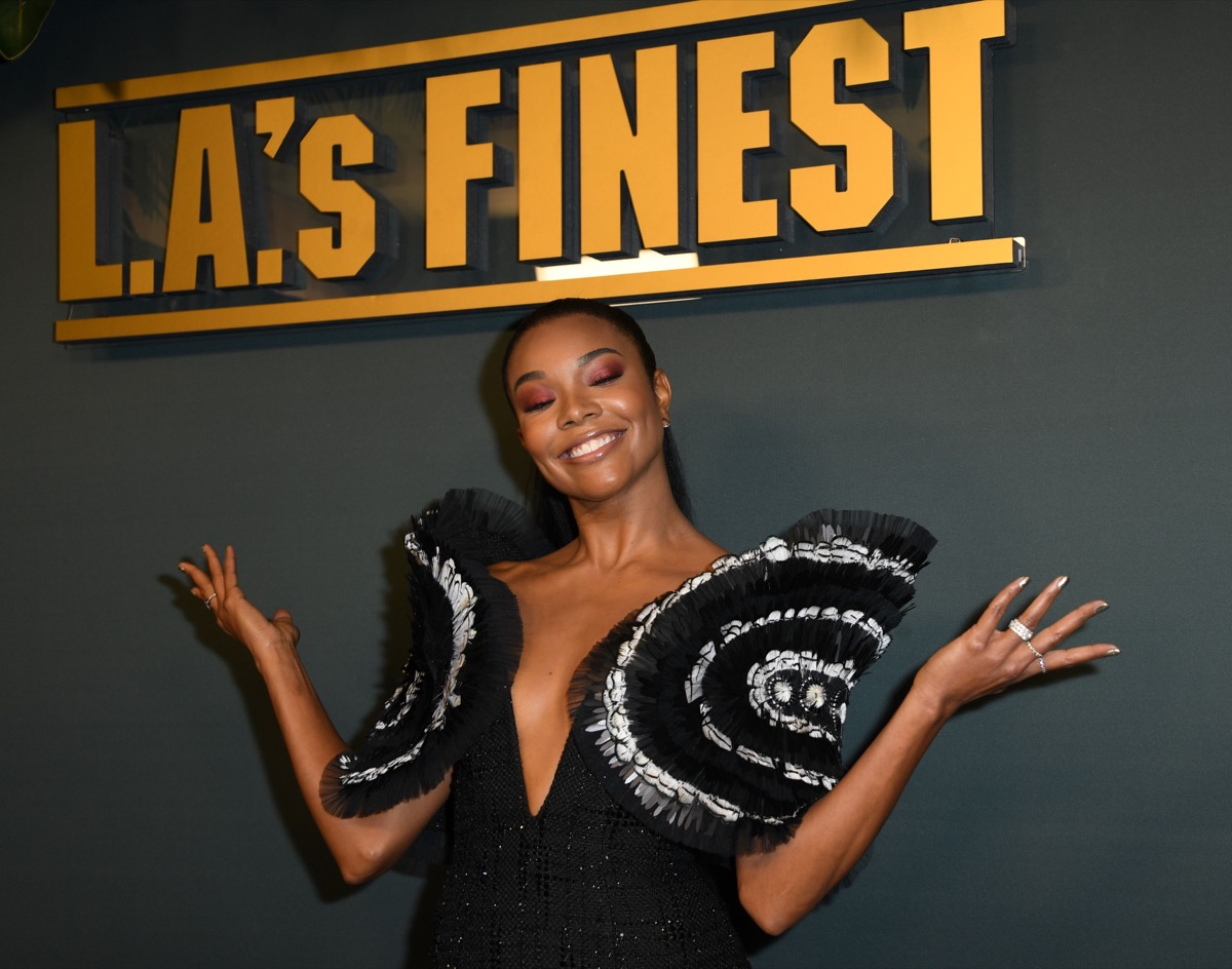 gabrielle union in oversized plunging top in front of la's finest sign