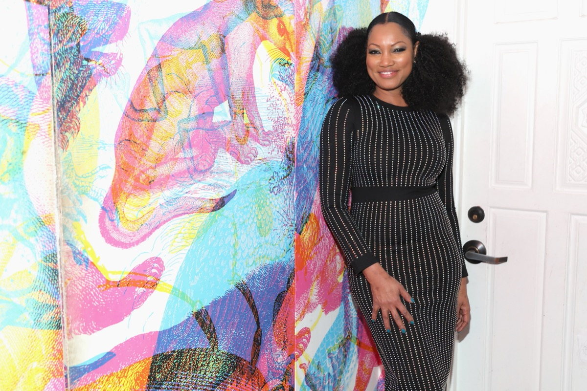 garcelle beauvais in black dress with vertical silver stripes standing in front of abstract painting