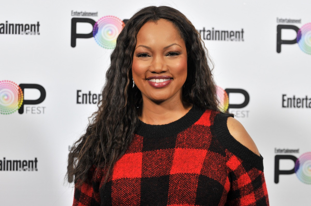 garcelle beauvais in red and black buffalo plaid sweater with exposed shoulders