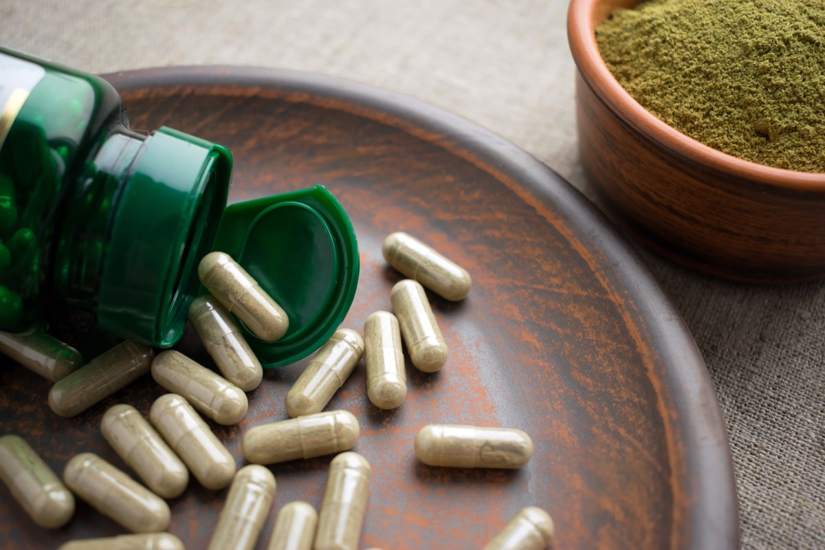 green tea supplement pills spilling out of green bottle onto wood plate