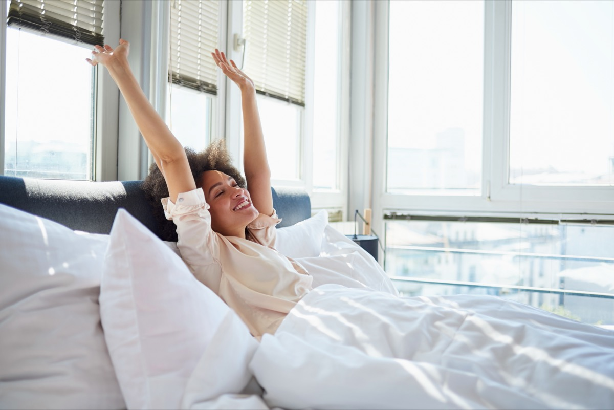 happy young woman in bed with white sheets stretching in front of windows in morning