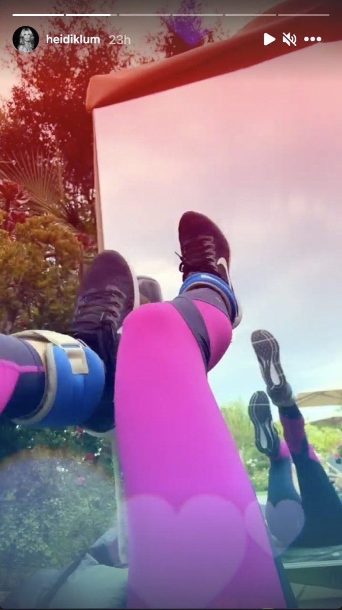 heidi klum in pink leggings with ankle weights bicycling her legs in front of a mirror