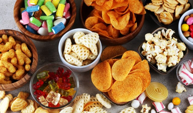 table covered in bowls of popcorn, chips, candy, and other junk foods