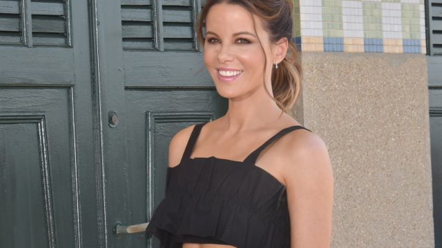 kate beckinsale outdoors in black crop top and white skirt smiling