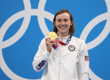 olympian katie ledecky holding up her medal at the 2021 tokyo olympics