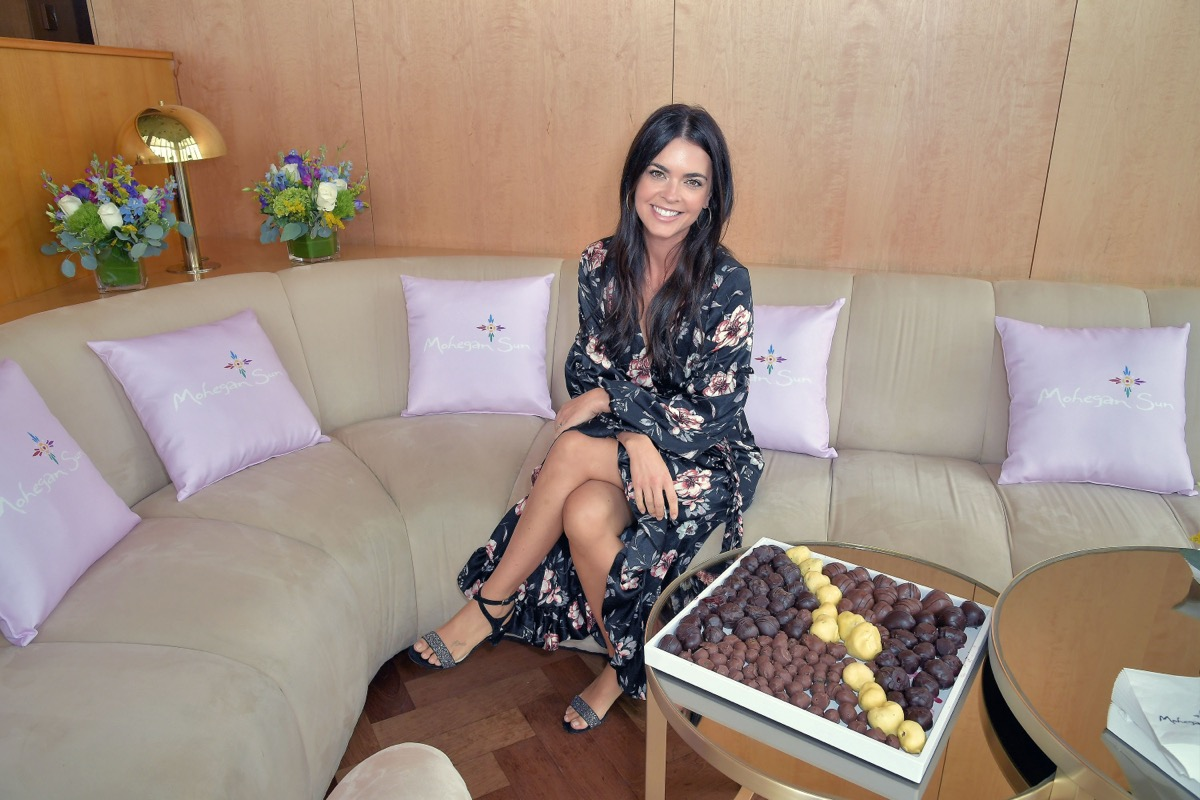 katie lee biegel sitting next to a table full of donut holes